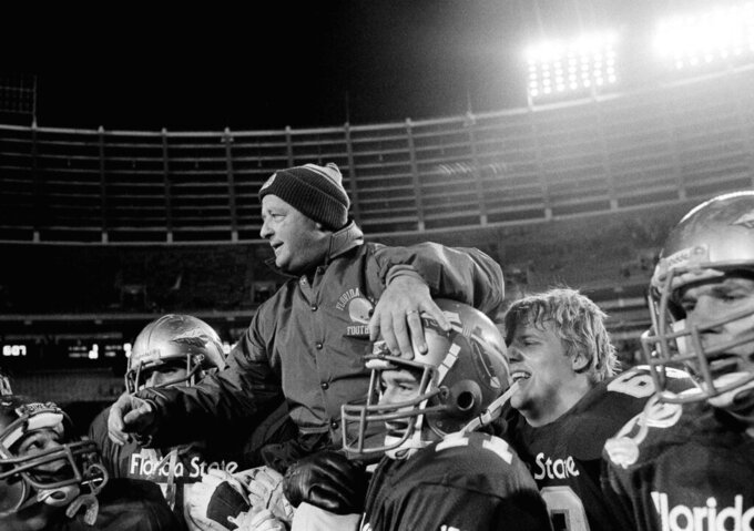 FILE - In this Dec. 31, 1983, file photo, Florida State coach Bobby Bowden is carried off the field by his team after they defeated North Carolina 28-3 in the Peach Bowl in Atlanta. Bowden, the folksy Hall of Fame coach who built Florida State into an unprecedented college football dynasty, has died. He was 91. Bobby's son, Terry, confirmed to The Associated Press that his father died at home in Tallahassee, Fla., surrounded by family early Sunday, Aug. 8, 2021. (AP Photo/Joe Holloway Jr., File)