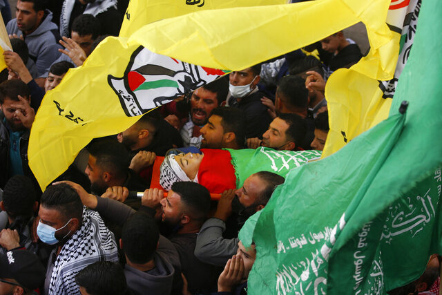 Relatives carry the body of a 13-year-old Ali Abu Alia who was shot dead by Israeli military forces during clashes with a stone-throwing Palestinains during his funeral in al-Mughair village near the West Bank city of Ramallah, Saturday, Dec. 5, 2020. (AP Photo/Majdi Mohammed)