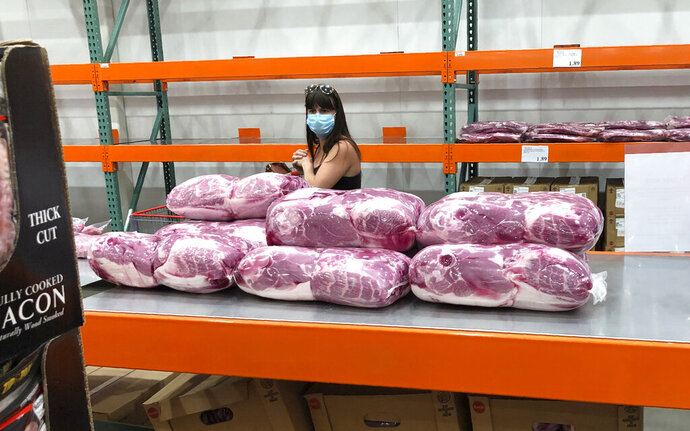 A shopper in a face mask looks over cuts of beef piled up in a cold room for purchase at a Costco warehouse store Tuesday, May 5, 2020, in west Denver.  The U.S. economy rebounded at an even-stronger pace in the July-September quarter than first reported but a resurgence in the coronavirus is expected to slow growth sharply in the current quarter with some analysts even raising the specter of a double-dip recession.  (AP Photo/David Zalubowski)