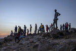 Tigray people who fled the conflict in Ethiopia's Tigray region, stand on a hill top over looking Umm Rakouba refugee camp in Qadarif, eastern Sudan, Thursday, Nov. 26, 2020. Ethiopia's prime minister said Thursday the army has been ordered to move on the embattled Tigray regional capital after his 72-hour ultimatum ended for Tigray leaders to surrender, and he warned the city's half-million residents to stay indoors and disarm. (AP Photo/Nariman El-Mofty)