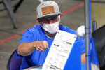 FILE - In this May 6, 2021 file photo, Maricopa County ballots cast in the 2020 general election are examined and recounted by contractors working for Florida-based company, Cyber Ninjas at Veterans Memorial Coliseum in Phoenix. For some conspiracy theorists, the 2020 election still hasn't ended. Trump supporters are pushing to re-examine ballots from November across the country, and finding success in swing states like Arizona and Georgia. Their efforts and sometimes misleading conclusions are being gleefully amplified by the former president.(AP Photo/Matt York, Pool)