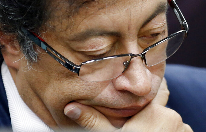 FILE - In this Dec. 4, 2018 file photo, Senator Gustavo Petro pauses during an interview at a local radio station in Bogota, Colombia. The former presidential candidate has adopted a low-key approach during the anti-government protests that started in late April 2021 ahead of his third run for Colombia's presidency. AP Photo/Fernando Vergara, File)
