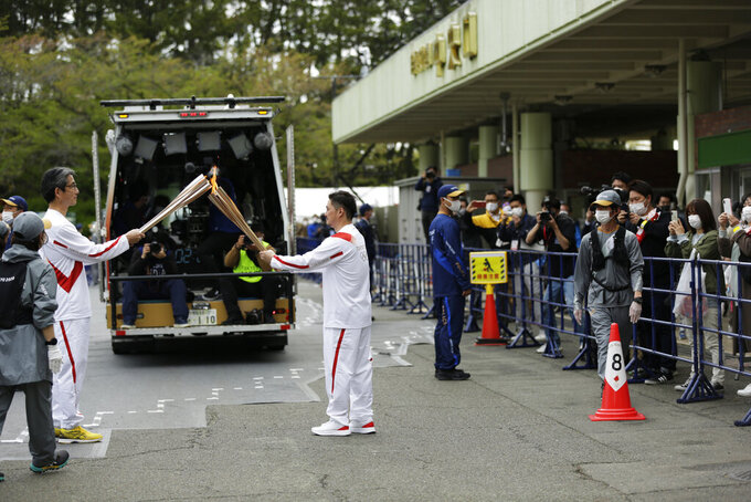 An Olympic torch relay runner, center, hands over the flame of the torch to the next runner during the first day of the Osaka round at a former Expo site in Suita, north of Osaka, western Japan, Tuesday, April 13, 2021. The Tokyo 2020 Olympic kick-off event which was rescheduled due to the coronavirus outbreak was yet rearranged to hold at the former Expo park, instead of public streets, to close off the audience from the even, following the mayor's decision as Osaka has had sharp increases in daily cases since early March. (AP Photo/Hiro Komae)