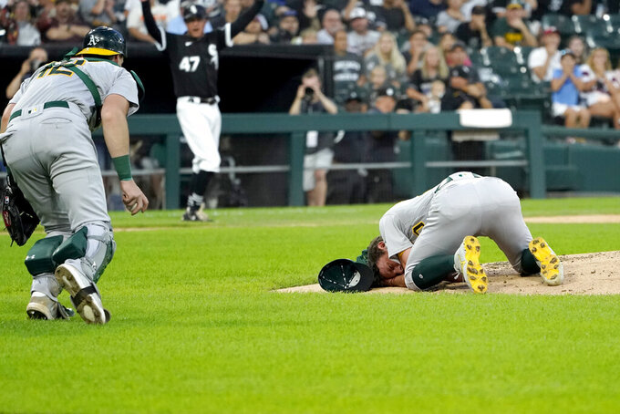 Oakland Athletics catcher Sean Murphy runs to starting pitcher Chris Bassitt after Bassitt was hit in the head from a ball hit by Chicago White Sox's Brian Goodwin during the second inning of a baseball game, Tuesday, Aug. 17, 2021, in Chicago. (AP Photo/Charles Rex Arbogast)