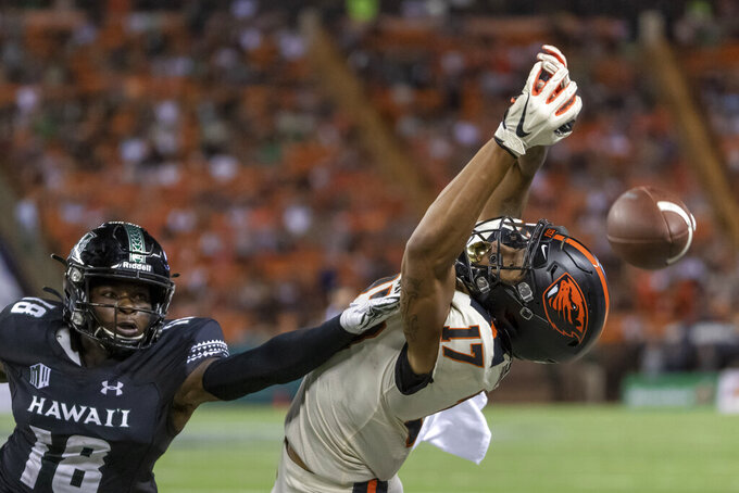Oregon State wide receiver Isaiah Hodgins (17) can't haul in a pass as Hawaii defensive back Cortez Davis (18) looks on during the second half of an NCAA college football game, Saturday, Sept. 7, 2019, in Honolulu. Hawaii beat Oregon State 31-28. (AP Photo/Eugene Tanner)