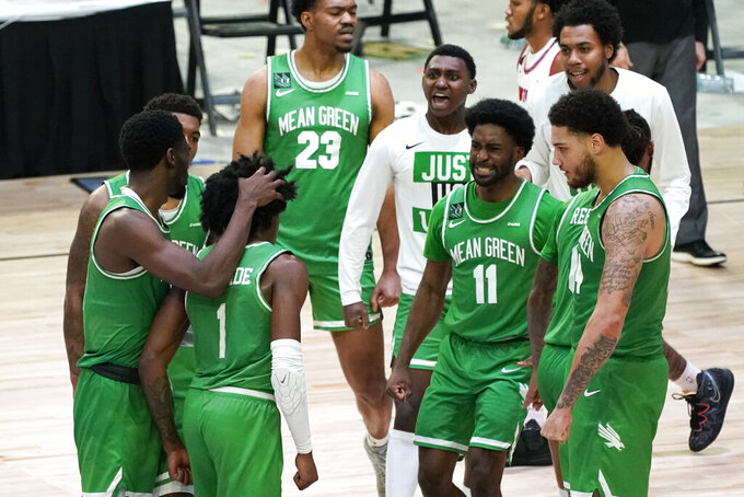 North Texas guard Mardrez McBride (1) celebrates with teammates after making a 3-point basket during the second half of the championship game against Western Kentucky in the NCAA Conference USA men's basketball tournament Saturday, March 13, 2021, in Frisco, Texas. (AP Photo/Tony Gutierrez)