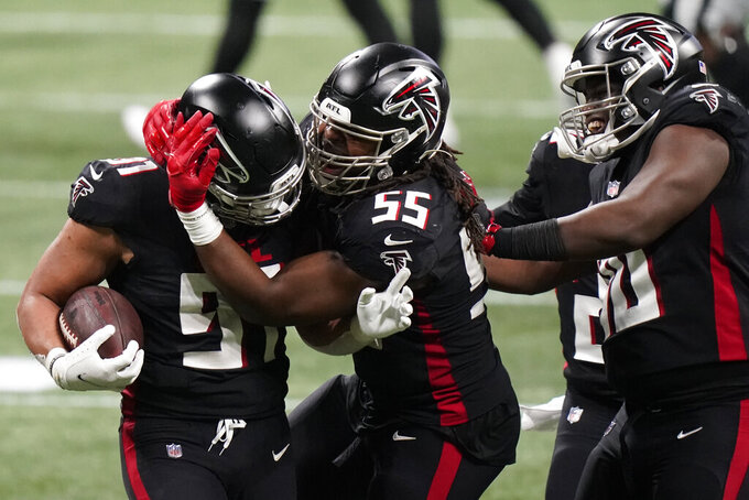 Atlanta Falcons defensive tackle Jacob Tuioti-Mariner (91) celebrates a fumble recovery with Atlanta Falcons defensive end Steven Means (55) during the first half of an NFL football game against the Las Vegas Raiders, Sunday, Nov. 29, 2020, in Atlanta. (AP Photo/Brynn Anderson)