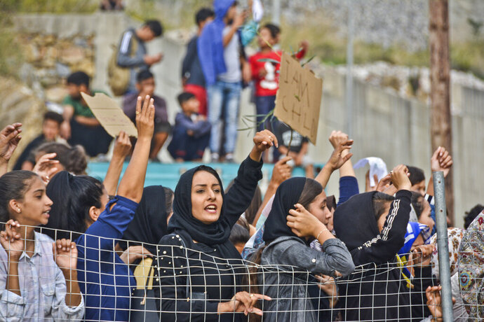 Refugees and migrants take part in a protest outside an overcrowded refugee camp on the Greek island of Samos, on Friday, Oct. 18, 2019. Overcrowding at island camps has continued to worsen despite an effort by the Greek government to move more asylum seekers to the mainland. (AP Photo/Michael Svarnias)