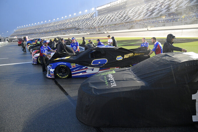Crew members prepare to push their cars off pit road after a NASCAR Cup Series auto race was postponed to the next day at Daytona International Speedway, Saturday, July 6, 2019, in Daytona Beach, Fla. (AP Photo/Phelan M. Ebenhack)