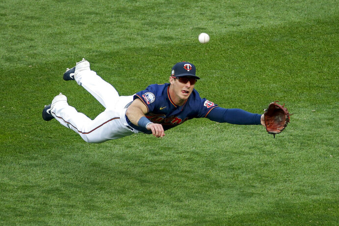 Minnesota Twins right fielder Brent Rooker dives for but misses a ball hit by Detroit Tigers' Jonathan Schoop for an RBI triple during the third inning of the second baseball game of a doubleheader Friday, Sept. 4, 2020, in Minneapolis. (AP Photo/Bruce Kluckhohn)