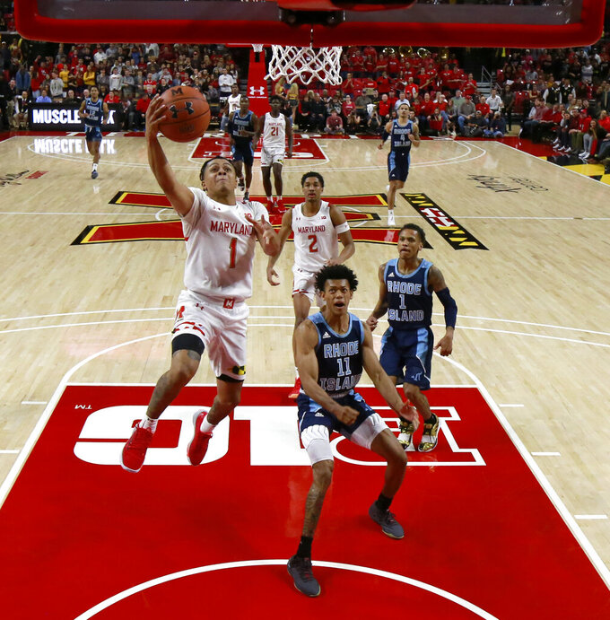 Maryland guard Anthony Cowan Jr. (1) goes up for a shot as Rhode Island guard Jeff Dowtin (11) and guard Fatts Russell (1) watch during the second half of an NCAA college basketball game Saturday, Nov. 9, 2019, in College Park, Md. Maryland won 73-55. (AP Photo/Julio Cortez)