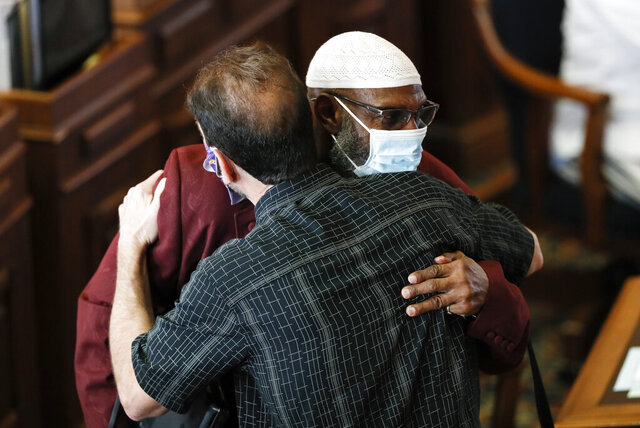 Rep. Ako Abdul-Samad, D-Des Moines, left, gets a hug from Rep. Bob Kressig, D-Cedar Falls, in the Iowa House chambers, Wednesday, June 3, 2020, at the Statehouse in Des Moines, Iowa. Lawmakers returned Wednesday after suspending the session when the coronavirus pandemic surfaced in Iowa in March, prompting state officials to close the state Capitol. (AP Photo/Charlie Neibergall)