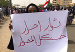 A Sudanese protester holds an Arabic placard that reads: