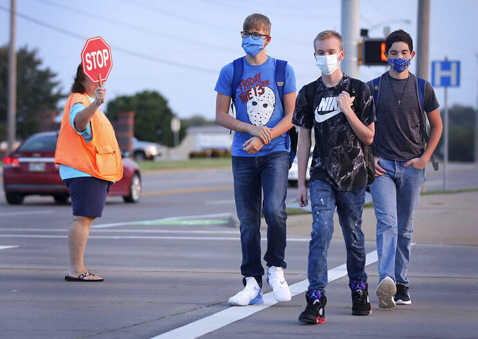 Freshmen Mason Mathis, left, Travis Ryan and Seth Wood make their way to school on the first day of in-person instruction at Owasso schools Thursday, Sept. 17, 2020 in Owasso, Okla. (Mike Simons/Tulsa World via AP)