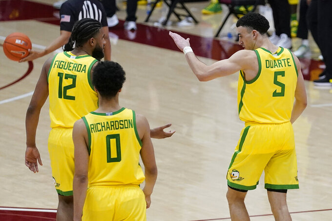 Oregon guard LJ Figueroa (12) celebrates with guard Chris Duarte (5) during the second half of the team's NCAA college basketball game against Stanford in Stanford, Calif., Thursday, Feb. 25, 2021. (AP Photo/Jeff Chiu)