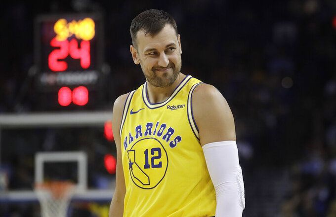 "FILE - In this Tuesday, April 2, 2019 file photo, Golden State Warriors center Andrew Bogut looks on during an NBA basketball game against the Denver Nuggets in Oakland, Calif.. Australian basketball player Andrew Bogut had hoped to finish his career in Tokyo last summer, but he announced his retirement in December, saying ""I just can't physically and mentally get to 2021."" (AP Photo/Jeff Chiu, file)"