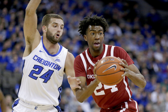 Oklahoma's Jamal Bieniemy, right, drives to the basket against Creighton's Mitch Ballock (24) during the first half of an NCAA college basketball game in Omaha, Neb., Tuesday, Dec. 17, 2019. (AP Photo/Nati Harnik)