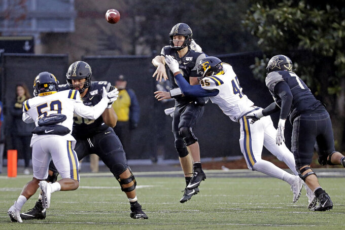 Vanderbilt quarterback Riley Neal throws as he is hit by ETSU defensive lineman Nasir Player (45) in the first half of an NCAA college football game Saturday, Nov. 23, 2019, in Nashville, Tenn. (AP Photo/Mark Humphrey)