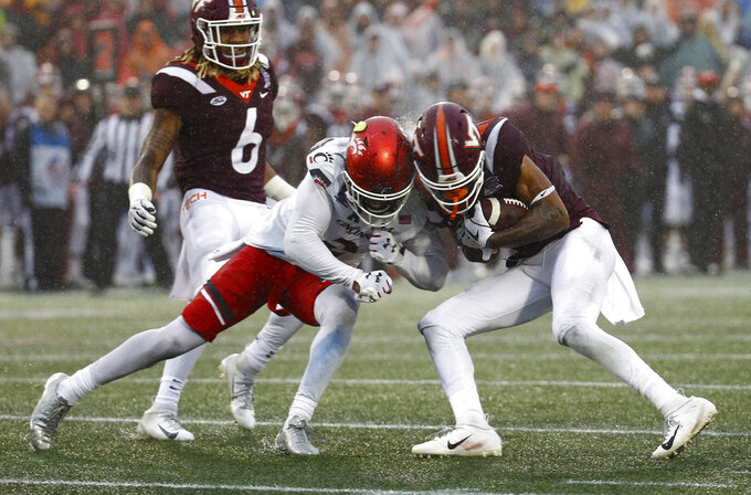Cincinnati cornerback Tyrell Gilbert, left, collides with Virginia Tech wide receiver Tre Turner as Turner rushes the ball in the second half of the Military Bowl NCAA college football game, Monday, Dec. 31, 2018, in Annapolis, Md. Gilbert was ejected from the game for targeting Turner on the play. (AP Photo/Patrick Semansky)