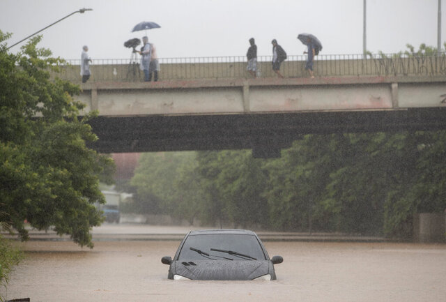 A car is stuck in a flooded street in Sao Paulo, Brazil, Monday, Feb. 10, 2020. Torrential downpour flooded the city, causing its main river to overflow its banks. (AP Photo/Andre Penner)