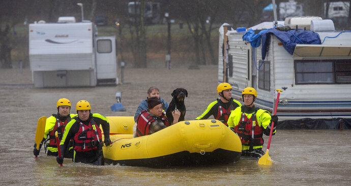 The Bristol Tennessee Fire Department's Swift Water Rescue team brings a couple and their 3 dogs to safety after the Shadrack Campgrounds flooded Thursday, Feb. 6, 2020 in Bristol Tennessee. (Andre Teague/Bristol Herald Courier via AP)