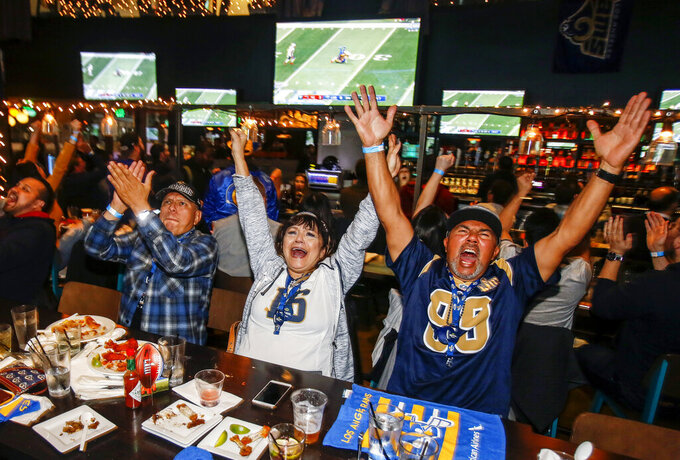 From left, Marco Perez, Susan Ballesteros and Rocky Ballesteros react during a viewing party for the Super Bowl 53 football game between the New England Patriots and the Los Angeles Rams in Los Angeles, Sunday, Feb. 3, 2019. (AP Photo/Ringo H.W. Chiu)