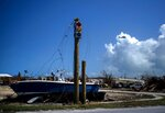 A boat sits on dry land next to a traffic light in the aftermath of Hurricane Dorian, in Abaco, Bahamas, Tuesday Sept. 17, 2019. Dorian hit the northern Bahamas on Sept. 1, with sustained winds of 185 mph (295 kph), unleashing flooding that reached up to 25 feet (8 meters) in some areas. (AP Photo/Ramon Espinosa)