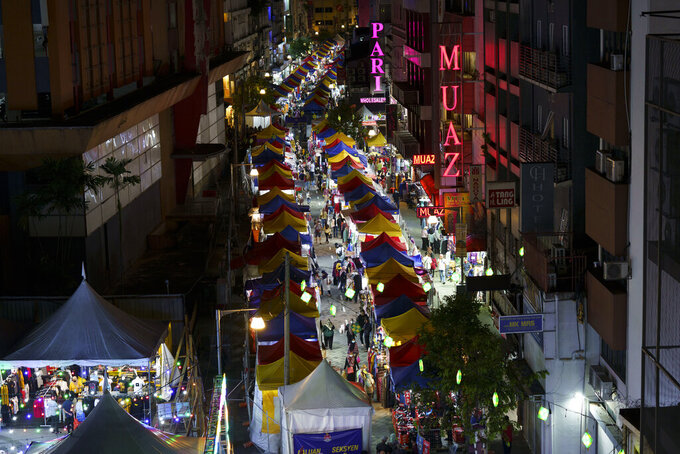 In this April 24, 2021, photo, shoppers walk through the outdoor Ramadan bazaar in Kuala Lumpur, Malaysia. Malaysian Prime Minister Muhyiddin Yassin announced Monday that the whole country will be placed under a near lockdown for about a month but all economic sectors will be allowed to operate. (AP Photo/Vincent Thian)