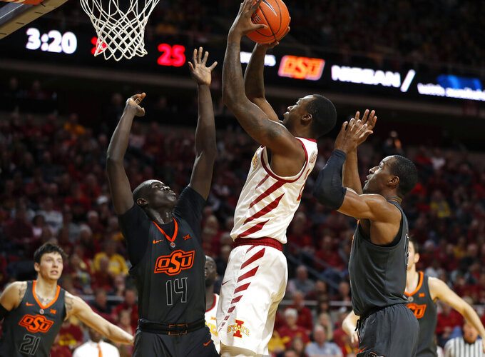 Iowa State forward Cameron Lard, center, shoots as Oklahoma State forwards Yor Anei, left, and Cameron McGriff, right, defend during the first half of an NCAA college basketball game, Saturday, Jan. 19, 2019, in Ames. (AP Photo/Matthew Putney)