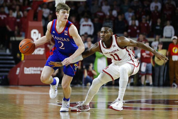 Kansas' Christian Braun (2) is defended by Oklahoma's De'Vion Harmon (11) during the first half of an NCAA college basketball game in Norman, Okla., Tuesday, Jan. 14, 2020. (AP Photo/Garett Fisbeck)