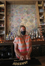 Danielle Savin, co-owner of a bar called Bob's Your Uncle, poses for a photo, Tuesday, June 30, 2020, at the bar in Miami Beach, Fla. Savin owns two bars that were forced to shut down for months in both New York and Miami Beach. When the pandemic first hit and New York was the country's epicenter she feared for that business, but months later the two states have flip-flopped. (AP Photo/Wilfredo Lee)