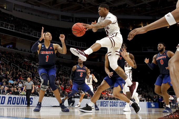 Mississippi State guard Lamar Peters passes around Liberty guard Caleb Homesley, left, during the second half of a first-round game in the NCAA men's college basketball tournament Friday, March 22, 2019, in San Jose, Calif. (AP Photo/Jeff Chiu)