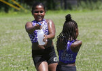 Dancers from the 4 Star Dance Studio Jazmyn Cawley-Zayas, 9, left, and Kymora McKoy-Johnson, 6, right, both of Boston, spray one another while cooling down after dancing in the Roxbury Unity Parade, Sunday, July 21, 2019, in Boston's Roxbury neighborhood. Temperatures during the parade reached the 90s. (AP Photo/Steven Senne)