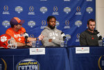 Clemson head coach Dabo Swinney, left, introduces linebacker Kendall Joseph, center, and wide receiver Hunter Renfrow, right, during a news conference at AT&T Stadium in Arlington, Texas, Monday, Dec. 24, 2018. Clemson is scheduled to play Notre Dame in the NCAA Cotton Bowl semi-final playoff Saturday. (AP Photo/Jim Cowsert)