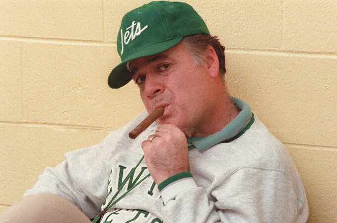 FILE - in this Dec. 31, 1986 file photo, New York Jets coach Joe Walton smokes a cigar during an interview at Hofstra University in West Hempstead, N.Y. Walton, the former New York Jets coach who built Robert Morris University's football program from the ground up, died Sunday, Aug. 15, 2021. He was 85. (AP Photo/W. Funches)