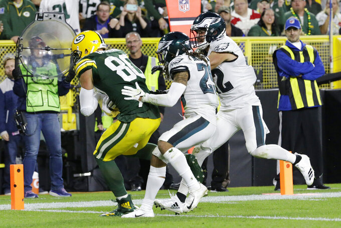 Green Bay Packers tight end Jimmy Graham (80) pulls in a catch for a touchdown while being defended by Philadelphia Eagles cornerback Avonte Maddox (29) and strong safety Andrew Sendejo (42) during the second half of an NFL football game Thursday, Sept. 26, 2019, in Green Bay, Wis. (AP Photo/Mike Roemer)