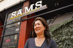 Jeannie Kim poses outside her restaurant in San Francisco on Friday, July 30, 2021. Thanks to a reworked menu and long hours, Jeannie Kim managed to keep her San Francisco restaurant alive during the coronavirus pandemic. That makes it all the more frustrating that she fears her breakfast-focused diner could be ruined within months by new rules that could make one of her top menu items — bacon — hard to get in California. (AP Photo/Eric Risberg)
