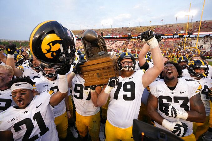 Iowa defensive lineman Zach VanValkenburg (97) and Iowa offensive lineman Jack Plumb (79) hoists the Cy-Hawk Trophy as their team shouts the Iowa fight song celebrating their 27-17 win over Iowa State in an NCAA college football game, Saturday, Sept. 11, 2021, in Ames, Iowa. (AP Photo/Matthew Putney)