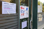 A poster, left, shows special summer opening hours at a medical laboratory Thursday, Aug.6, 2020 in Ville d'array, west of Paris. With virus cases rising anew, France is struggling to administer enough tests to keep up with demand. One reason: Many testing labs are closed so that their staff can take summer vacation, just as signs of a second wave build. (AP Photo/Bertrand Combaldieu)