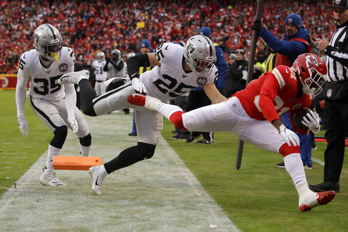 Kansas City Chiefs running back Darrel Williams (31) scores a touchdown against Oakland Raiders safeties Erik Harris (25) and Curtis Riley (35) during the first half of an NFL football game in Kansas City, Mo., Sunday, Dec. 1, 2019. (AP Photo/Charlie Riedel)