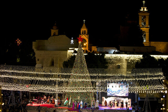Palestinian Christians celebrate the lighting of a Christmas tree outside the Church of the Nativity, traditionally believed by Christians to be the birthplace of Jesus Christ in the West Bank city of Bethlehem, Saturday, Nov. 30, 2019. The Palestinian Health Ministry has recommended strict limits on Christmas celebrations in Bethlehem this year due to the coronavirus outbreak. Celebrations in the biblical town revered by Christians as Jesus' birthplace are usually attended by thousands of people from around the world. In its recommendations Saturday, Nov. 21, 2020 it said religious services on Christmas Eve should also have limited attendance. (AP Photo/Majdi Mohammed)