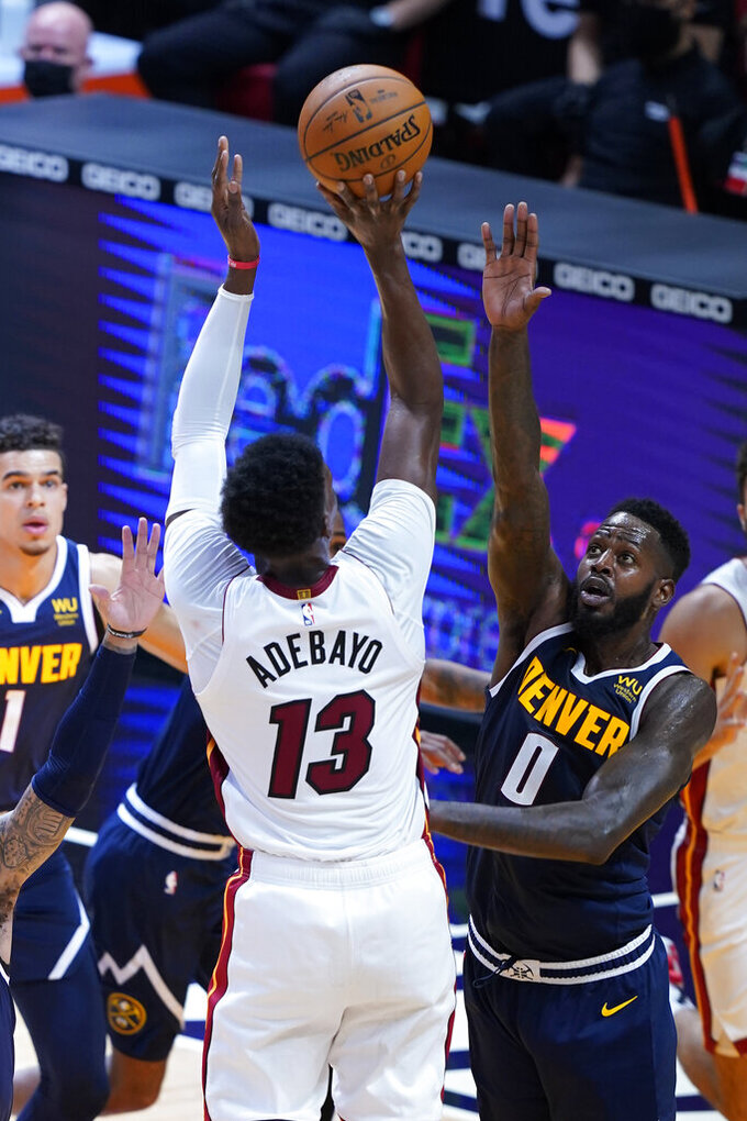 Miami Heat center Bam Adebayo (13) aims for a basket as Denver Nuggets forward JaMychal Green (0) defends during the first half of an NBA basketball game, Wednesday, Jan. 27, 2021, in Miami. (AP Photo/Marta Lavandier)
