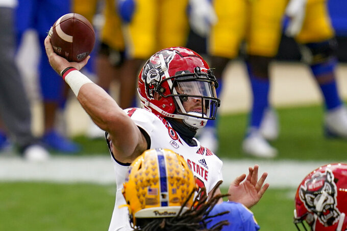 North Carolina State quarterback Devin Leary (13) gets a pass away as Pittsburgh Panthers defensive lineman Patrick Jones II (91) pressures in the first half of an NCAA college football game, Saturday, Oct. 3, 2020, in Pittsburgh. (AP Photo/Keith Srakocic)
