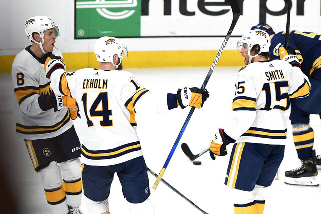 Nashville Predators center Kyle Turris (8) and defenseman Mattias Ekholm (14), of Sweden, celebrate after Craig Smith (15) scored the go-ahead goal against the Buffalo Sabres during the third period of an NHL hockey game Saturday, Jan. 18, 2020, in Nashville, Tenn. The Predators won 2-1. (AP Photo/Mark Zaleski)