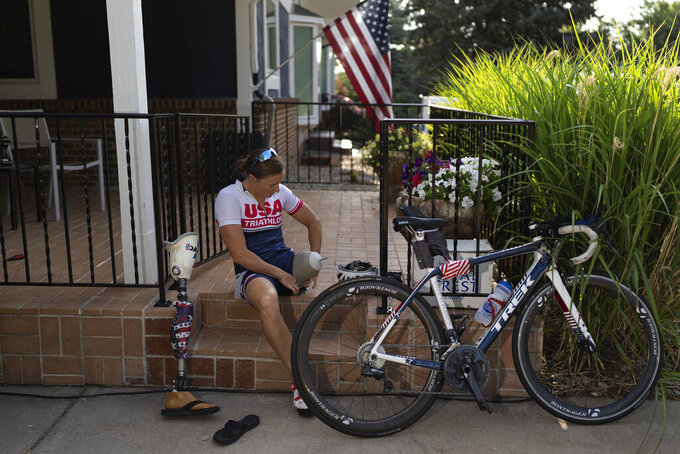 Melissa Stockwell prepares to ride her bicycle as part of her daily training session in her home in Colorado Springs, Colo., on Saturday, Aug. 7, 2021. She's a public figure who has done countless interviews and a sought-after speaker who knows to avoid controversy. Ask her about America's pullouts from Iraq and Afghanistan and she effortlessly shifts the conversation to patriotism and her family. (AP Photo/Emilio Morenatti)