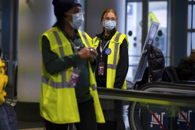 FILE - In this Friday, Jan. 24, 2020 file photo, airport employees wear face masks in Terminal 5 at O'Hare International Airport in Chicago. On Friday, Jan. 31, 2020, The Associated Press reported on stories circulating online incorrectly asserting that chlorine dioxide will help get rid of the new virus from China. The U.S. Food and Drug Administration warns that drinking products containing the chemical can cause nausea, vomiting, diarrhea and symptoms of severe dehydration. (E. Jason Wambsgans/Chicago Tribune via AP)