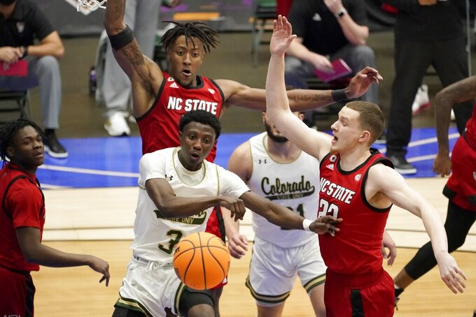 Colorado State guard Kendle Moore (3) is forced to pass the ball from beneath the basket as North Carolina State's Manny Bates, rear, and Max Farthing (22) defend during the first half of an NCAA college basketball game in the quarterfinals of the NIT, Thursday, March 25, 2021, in Frisco, Texas. (AP Photo/Tony Gutierrez)