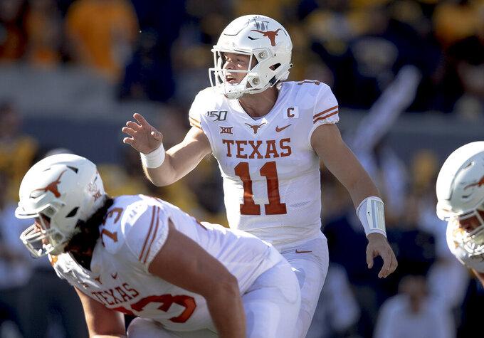 Texas quarterback Sam Ehlinger (11) shouts to his lineman during an NCAA football game against West Virginia, Saturday, Oct. 5, 2019, in Morgantown, W.Va. (Nick Wagner/Austin American-Statesman via AP)