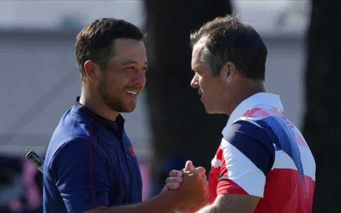 Xander Shauffele of United States, left, is congratulated by Paul Casey of Great Britain after winning Gold in the Men's Golf event at the 2020 Summer Olympics on Sunday, Aug. 1, 2021, in Kawagoe, Japan. (AP Photo/Andy Wong)