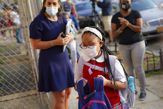 FILE - In this Sept. 9, 2020, file photo, students wear protective masks as they arrive for classes at the Immaculate Conception School while observing COVID-19 prevention protocols, in the Bronx borough of New York. (AP Photo/John Minchillo)